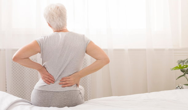 Senior woman holding her painful back in bed