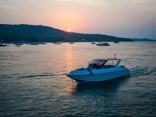 White motor boat at Sunset on Thailand sea Wall mural