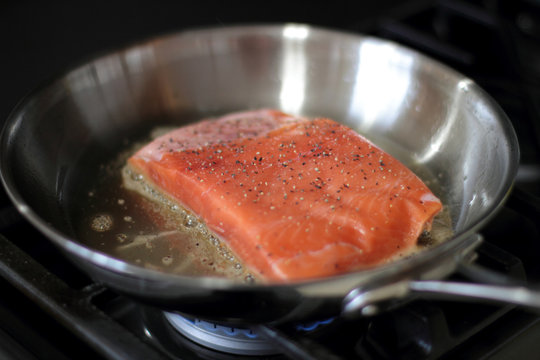 Wild caught King salmon frying in a pan with the skin side down.