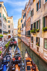 Fototapete - Narrow beautiful street with parked gondolas, Venice, Italy. Scenic vertical view of Venice canal in summer. Vintage houses and cityscape of Venice. Romantic water tourist trip across old Venice city.