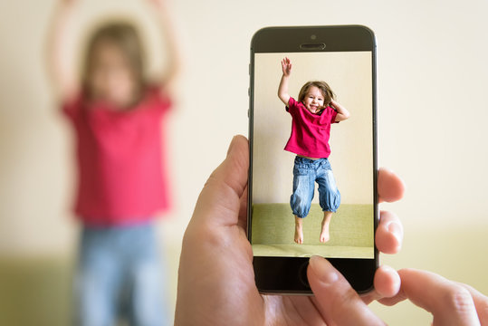 Funny child jump on couch. Mother taking photo of baby girl with her mobile phone. Photography of happy three-year-old kid playing and jumping at home. Adorable toddler with long hair dances on sofa.