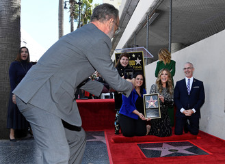 Tom Hanks takes a photo with his cellphone as his wife Rita Wilson poses during a ceremony to honor her with a star on Hollywood's Walk of Fame in Los Angeles