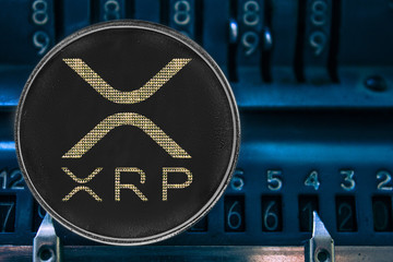 Coin cryptocurrency XRP against the numbers of the arithmometer. ripple