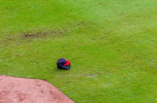 A Baseball Hat and Glove on Field in green grass by baseline