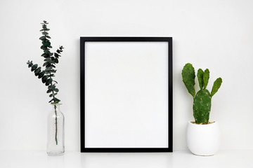 Mock up black frame with cactus and branches on a shelf or desk. White shelf and wall. Portrait frame orientation.