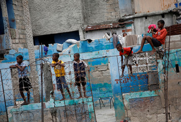 Children look at people as they march to protest against the Government in Port-au-Prince