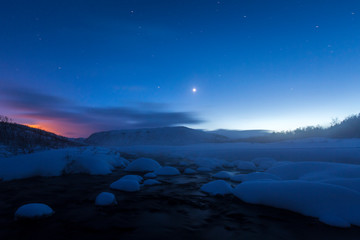 Fotobehang Chocoladebruin Water stream with rocks in a winter landscape in twilight.