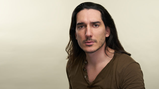 Portrait of latino handsome man with long black hair and green t shirt in studio