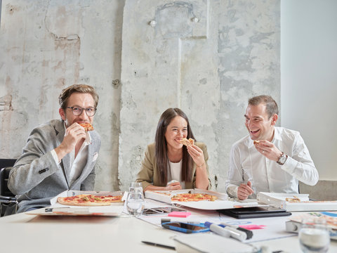 Happy colleagues having lunch break with pizza in conference room