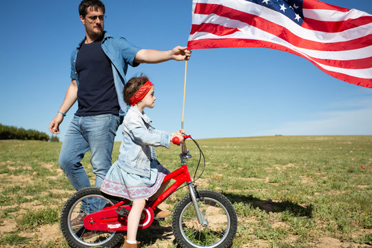 Man and daughter with bicycle and American flag on field in remote landscape