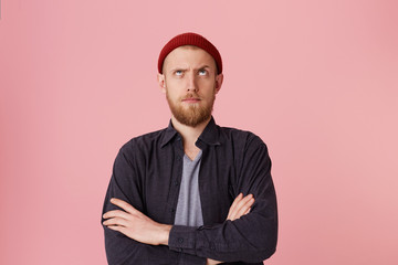 Photo of questioning bearded man in basic shirt, with red hat, with folded arms, look up with one raised eyebrow over pink background.