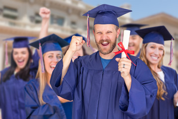 Proud Male Graduate in Cap and Gown In Front of Other Graduates