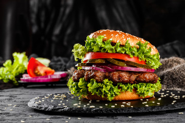 Fototapeta Beef burger with tomatoes, red onions, cucumber and lettuce on black slate over dark background. Unhealthy food obraz