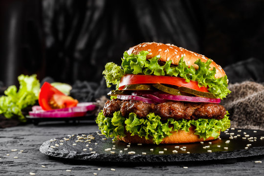 Beef burger with tomatoes, red onions, cucumber and lettuce on black slate over dark background. Unhealthy food