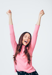 Happy young woman celebrating success with arms up isolated on white background