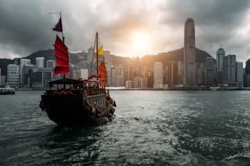 Wall Mural - Hong Kong City skyline with tourist sailboat. View from across Victoria Harbor Hong Kong.