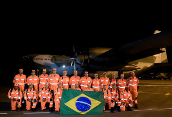 Brazilian firefighters pose for picture before their trip to Mozambique to help search for victims of cyclone Idai at the Pampulha airport in Belo Horizonte