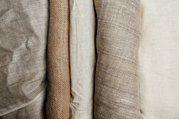 Obraz Natural fabrics from organic colors of flax and cotton in rolls, homespun textile handmade. Burlap and canvas for eco, rustic, boho, hygge decor - fototapety do salonu