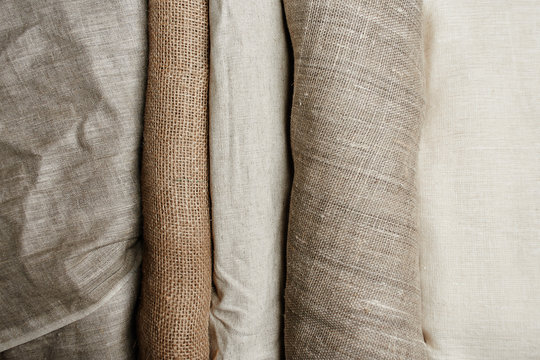 Natural fabrics from organic colors of flax and cotton in rolls, homespun textile handmade. Burlap and canvas for eco, rustic, boho, hygge decor