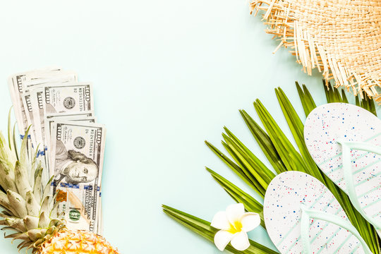 Travel flat lay items: one hundred dollars bills, beach slippers, fresh pineapple, tropical flower and palm leaf lying on green background. Place for text. Top view. Summer concept