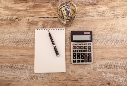 dollars in a jar, calculator, notebook and pen on the table