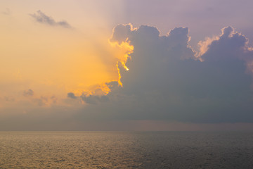 The sun is rising being storm clouds and filtering through, over the Andaman sea in Thailand.