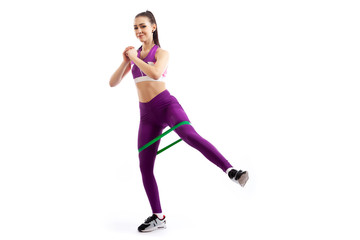 A dark-haired woman coach in a sporty purple  short top and gym leggings makes lunges  by the feet forward with sport fitness rubber bands,  stretch legs on a  white isolated background in studio