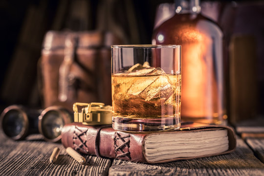 Closeup of whisky with ice on old journal