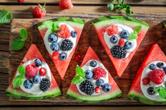 Sweet watermelon pizza with blueberries, raspberries and cream