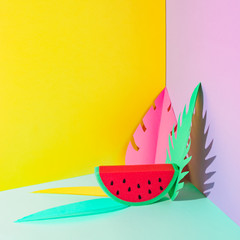 Watermelon slice with strong fashion shadow and colorful palm leaves. Bright creative concept of luxury relax with fruit on the tropical beach.  Minimalism
