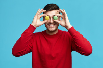 Food, pastry, joy and fun concept. Picture of funny unshaven young brunette male in red sweatshirt posing isolated at blue studio wall, holding two round almond cookies at his eyes and smiling happily