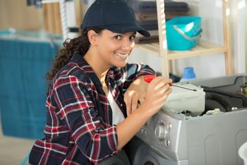 female technician fixing washing machine