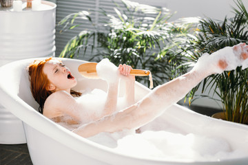 Vivacious emotional young woman with red hair bun taking bath at home, being in good temper,...