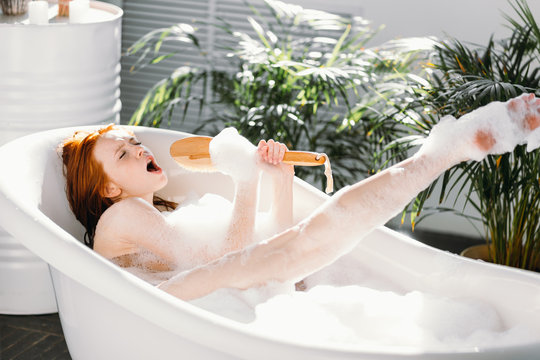 Vivacious emotional young woman with red hair bun taking bath at home, being in good temper, singing a song holding body brush as a microphone, giving way to her talant and joy