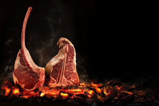 Whole T-Bone steak cooking on embers. Black background.