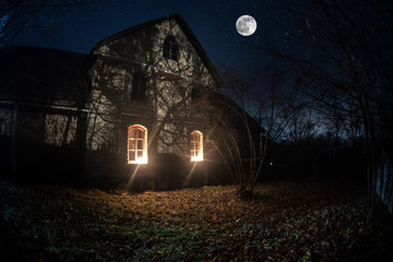Old house with a Ghost in the forest at night or Abandoned Haunted Horror House in fog. Old mystic building in dead tree forest. Trees at night with moon. Surreal lights. Wall mural