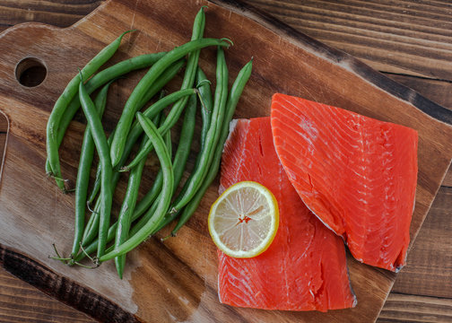 Sock eyed salmon with organic green beans and lemon on wooden cutting board