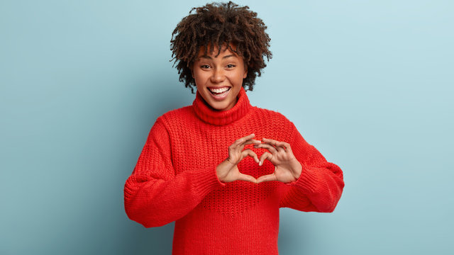 Indoor shot of attractive female model shapes heart symbol with both hands, demonstrates gesture of love to someone, wears red winter clothes, smiles positively, isolated over blue background