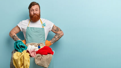 Indoor shot of indignant man has thick red beard, busy with housework, stands in front of basin with pile of dirty linen, has tattooed arms, poses over blue studio background, free space right