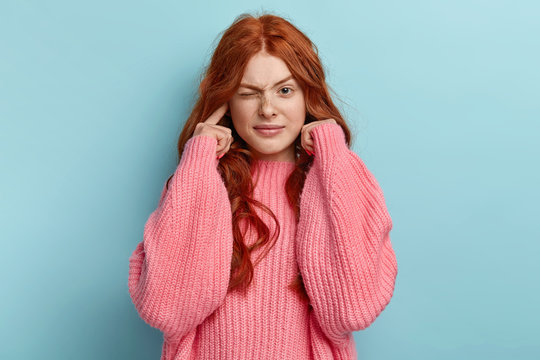 Young lovely ginger female musician plugs ears as hears awful noise or music, squints face, has long wavy foxy hair, wears oversized pink jumper, avoids loud sound, ignores something unpleasant