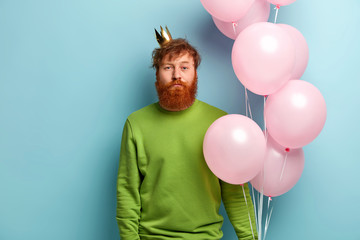 Confident serious red haired male model in green clothes, crown on head, carries bundle of pink balloons, being present of festive celebration, organizes balloon party, poses over blue background