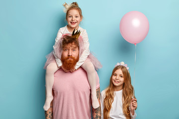 Children and celebration concept. Bearded unshaven man gives piggy back to small daughter, long haired girl stands near and holds pink balloon, have family party birthday day, have fun indoors
