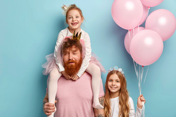 Family, friendly relationships, fatherhood and celebration concept. Tired red haired father gives piggyback to small daughter, celebrates birthday party with children, enjoy happy moments together. Wall mural