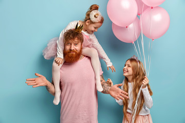How to celebrate? Uncertain bearded man with ginger beard gestures doubtfully, plays with two small kids, celebrate holiday. Playful naughty girl on fathers shoulders stretches hand to sister