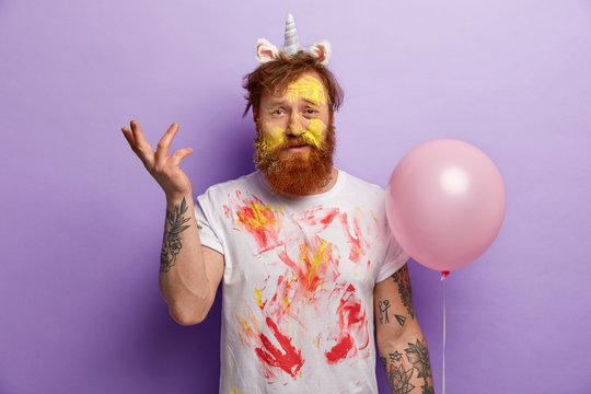 Image of puzzled displeased indignant man with ginger hair and beard, raises hand hesitantly, wears white t shirt dirty with paints, carries balloon, stands over purple background. Festive day