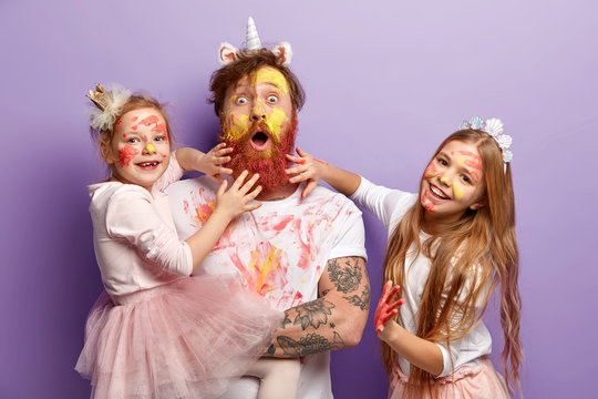 Funny two girls paint fathers beard with colorful paints, have fun together, celebrate holiday, wear festive apparel, have ginger hair, look alike, stand over purple background. Childhood concept