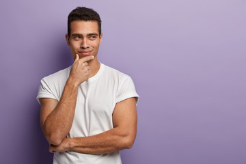 Waist up shot of handsome man with muscular arms, holds chin, smiles and dreams about something, has intention to make surprise, wears casual white t shirt, models indoor, empty space aside.