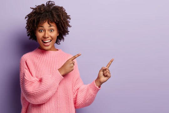 Waist up shot of positive lovely woman with Afro hairstyle, points away with both fore fingers, shows somethig on blank space, has joy expression, wears loose pink jumper, gestures over violet wall