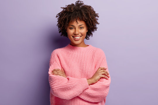 Photo of self confident pleased dark skinned woman keeps arms folded, smiles gladfully while watches funny programme, has natural appealing beauty, wears oversized pink jumper, poses indoor.