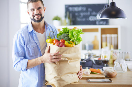 Man holding paper bag full of groceries on the kitchen background. Shopping and healthy food concept